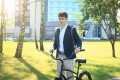 Businessman walking with bike in street after work. Businessman walking with bike in street after work Royalty Free Stock Images