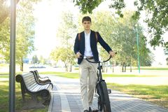 Businessman walking with bike in street after work. Businessman walking with bike in street after work Stock Photo