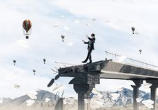Concept of hidden risks and dangers. Businessman walking blindfolded among flying paper planes on concrete bridge with huge gap as symbol of hidden threats and Royalty Free Stock Image