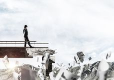 Concept of hidden risks and dangers. Businessman walking blindfolded among flying papers on concrete bridge with huge gap as symbol of hidden threats and risks Stock Photo