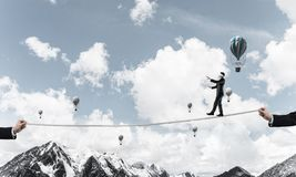 Hidden risks,dangers and business support concepts. Businessman walking blindfolded on rope above high mountains as symbol of hidden threats and support. Flying royalty free stock image