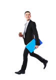 Businessman walking with blue folder and cup of coffee Royalty Free Stock Photos