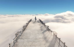 Businessman walking on a bridge. Young businessman walking on a bridge placed overclouds to heaven Stock Photography