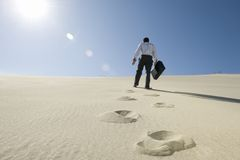Businessman Walking With Briefcase In Desert Stock Image