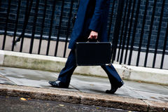 Businessman walking with briefcase. A businessman walks holding a black briefcase Stock Photo
