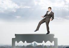 Businessman walking carefully on old razor blade Stock Photo
