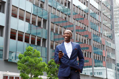 Businessman walking with  cell phone in the city Royalty Free Stock Images