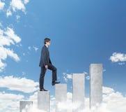 Businessman walking on chart Stock Photo