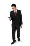 Businessman walking, checking on  phone. Young handsome businessman walking and checking on his cellphone, full body shot,  on white background Stock Photography