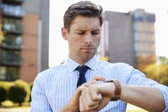 Businessman Walking Through City Park Looking At Smart Watch stock photos
