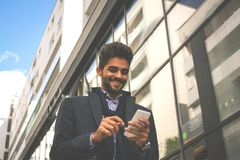 Businessman walking on city street and reading messages on. Happy businessman walking on city street and reading messages on smart phone stock photo