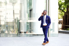 Businessman walking in the city using mobile phone Stock Photo