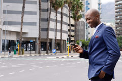 Businessman walking in the city and using mobile phone Stock Photo