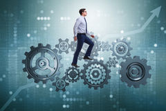 The businessman walking on cogwheels in teamwork concept Royalty Free Stock Photos