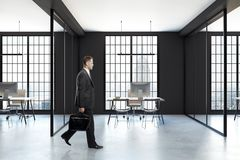 Man walking in office. Businessman walking in contemporary coworking office interior with city view and equipment. 3D Rendering Royalty Free Stock Photography