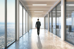 Businessman walking on corridor. Businessman walking on empty corridor interior. 3D Rendering Stock Photo