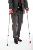 Businessman Walking On Crutches Royalty Free Stock Image