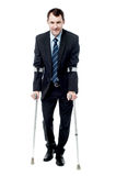 Businessman walking with crutches Royalty Free Stock Photography