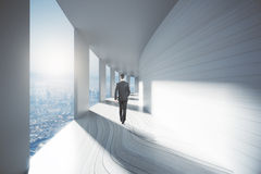 Businessman walking down corridor. Businessman walking down bright empty corridor interior with city view and sunlight. 3D Rendering Stock Photos