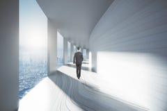 Businessman walking down corridor Stock Photos