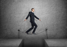 Businessman walking on drawn tightrope over the gap Stock Photos