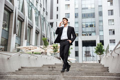 Businessman walking and drinking take away coffee in the city Royalty Free Stock Photography