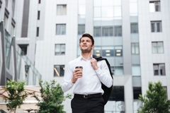 Businessman walking and drinking take away coffee outdoors Stock Image