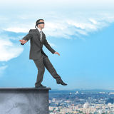 Businessman walking from edge of building roof Royalty Free Stock Image
