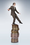 Businessman walking from edge of coins pile Stock Image