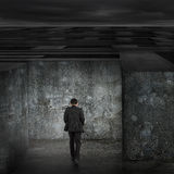 Businessman walking enter dark huge maze with cloudy sky Royalty Free Stock Image