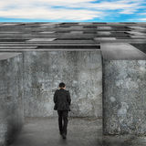 Businessman walking enter the huge maze with blue sky clouds Royalty Free Stock Photo
