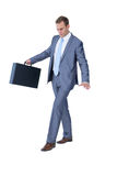Businessman walking in equilibrium with suitcase. On white background Royalty Free Stock Photo