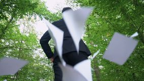 Businessman walking in forest and throwing away all papers, enjoying freedom