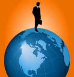 Businessman walking on globe Stock Photo