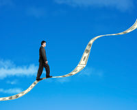 Businessman walking on growing money trend with blue sky backgro Royalty Free Stock Photos