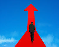 Businessman walking on growing red arrow in sky Stock Images
