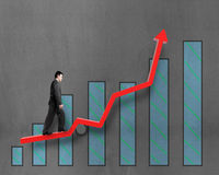 Businessman walking on growth red arrow with chart Royalty Free Stock Images