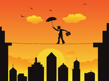 Businessman walking a high wire tightrope. A businessman walking on the high wire tightrope at sunset scene Stock Photos