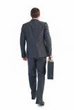 Businessman walking with his briefcase Royalty Free Stock Image