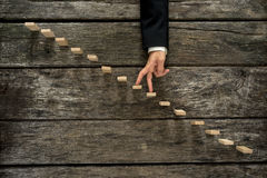 Businessman walking his fingers up steps. Businessman walking his fingers up wooden steps or pegs resembling a staircase mounted in rustic wooden boards in a Royalty Free Stock Photos