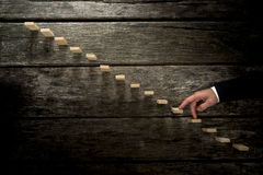 Businessman walking his fingers up wooden steps towards light Royalty Free Stock Photography
