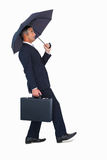 Businessman walking and holding briefcase under umbrella Royalty Free Stock Images