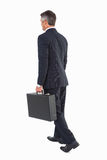 Businessman walking and holding briefcase Stock Photo