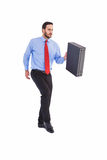 Businessman walking while holding briefcase Stock Photography