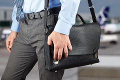Businessman walking and holding  a  leather briefcase in his han Royalty Free Stock Images