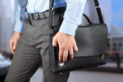 Businessman walking and holding  a  leather briefcase in his han Stock Image