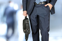 Businessman walking and holding  a  leather briefcase in his han Royalty Free Stock Photo