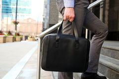 Businessman walking and holding  a  leather briefcase in his handss Modern city behind Stock Photography