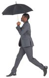 Businessman walking and holding umbrella Royalty Free Stock Image