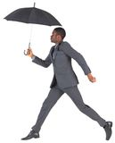 Businessman walking and holding umbrella Royalty Free Stock Images